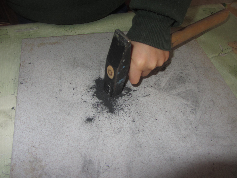 Alle prese nel frantumare i pezzetti di carbone